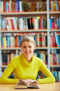 Portrait Of Clever Student With Open Book Looking At Camera In College Library
