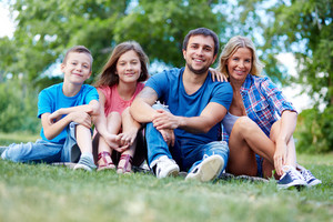 Photo Of Happy Family Of Four Sitting On Grass During Summer Rest