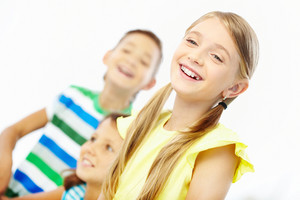 Portrait Of Laughing Girl With Two Classmates At Background
