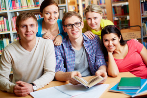 Portrait Of Friendly Students Sitting In College Library And Looking At Camera