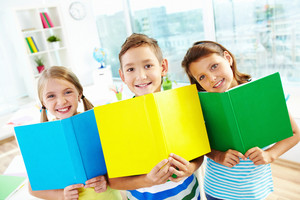 Portrait Of Happy Classmates With Open Books Smiling At Camera In Classroom