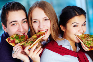 Image Of Happy Teenage Friends Eating Pizza And Looking At Camera