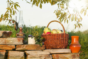 Basket Of Apple With Old Lamp And Mug Of Plums