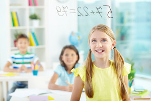 Portrait Of Lovely Girl Looking At Sums On Transparent Board With Schoolmates On Background