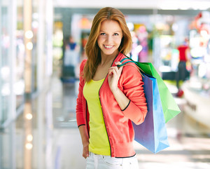Portrait Of Happy Girl With Colorful Shopping Bags Looking At Camera