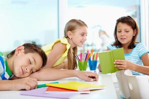 Sleeping Boy On Background Of Two Chatting Classmates