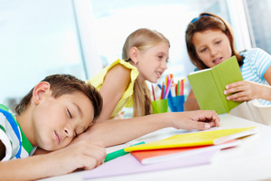 Sleeping Boy On Background Of Two Chatting Classmates