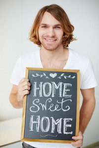 Photo Of Young Man Holding Small Board With Message About Home