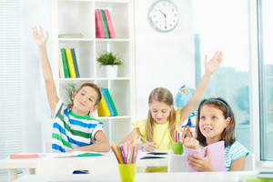 Portrait Of Clever Schoolkids Raising Hands At Workplace With Their Classmate Near By
