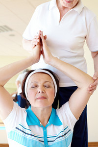 Portrait Of Aged Female Doing Yoga Exercise With Her Sports Instructor In Gym