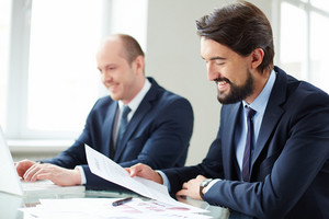 Image Of Young Businessman Reading Contract On Background Of His Colleague Typing