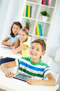 Portrait Of Curious Boy And His Two Schoolmates On Background Looking At Something Attentively At Lesson