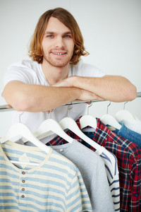 Photo Of Young Man Looking At Camera By The Hangers With Clothes