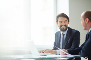 Image Of Handsome Businessman Typing And Communicating With To His Colleague At Meeting