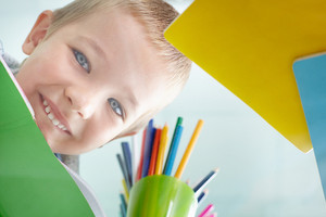 Happy Schoolkid Looking At Camera Through Glass Table With Multicolored Pencils On It