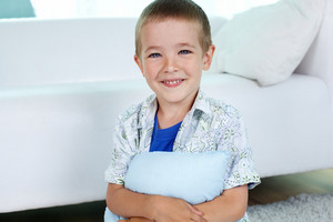 Portrait Of Happy Little Boy With Pillow Looking At Camera