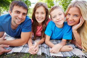 Photo Of Happy Family Of Four Relaxing In Park In Summer
