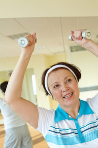 Portrait Of Aged Woman Doing Physical Exercise With Barbells