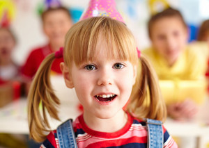 Happy Girl In Birthday Cap Looking At Camera With Her Friends On Background