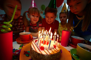 Group Of Adorable Kids Sitting In The Darkness And Looking At Birthday Cake With Burning Candles