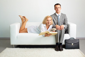 Photo Of Serious Man Sitting On Sofa With Happy Woman With Open Book Lying Near By