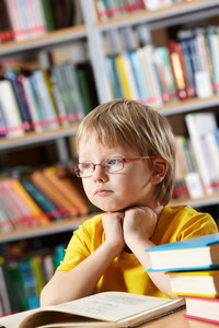 Portrait Of Clever Boy Thinking While Reading Book In Library