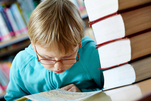 Portrait Of Cute Boy Looking At Map In Library