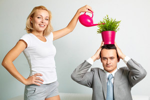 Photo Of Serious Man With Plant On Head Being Watered By Happy Woman