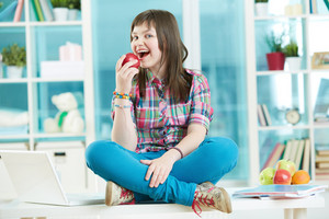 Pretty Teenage Girl Sitting On The Desk And Biting A Fresh Apple