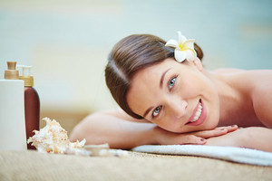 Happy Girl With Frangipani Flower In Hair Looking At Camera While Relaxing In Spa Salon