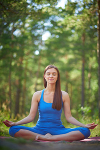 Portrait Of Meditating Woman Relaxing In Pose Of Lotus Outdoors