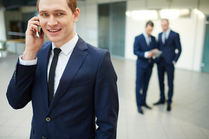 Young Businessman Calling And Looking At Camera In Working Environment