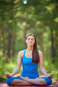 Portrait Of Calm Woman Sitting In Pose Of Lotus In Natural Environment
