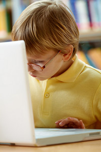 Portrait Of Serious Schoolkid Working With Laptop