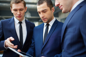 Image Of Three Young Businessmen Discussing Document In Touchpad At Meeting