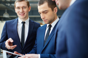 Group Of Businessmen Discussing Document In Touchpad At Meeting