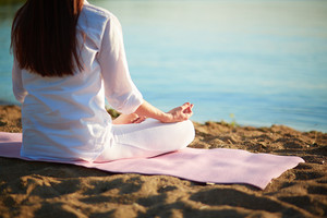 Back Of Meditating Woman Relaxing In Pose Of Lotus Outdoors
