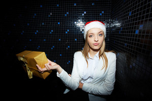 Dissatisfied Businesswoman In Santa Cap Holding Packed Present
