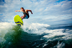 Male Surfer Riding On Waves In The Sea