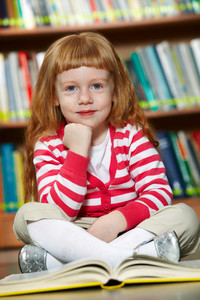 Portrait Of Smart Girl Sitting On The Floor In Library With Open Book In Front