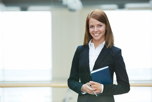 Portrait Of Young Businesswoman With Notepad And Pen Looking At Camera