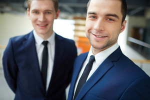 Young Businessman Looking At Camera With His Colleague On Background