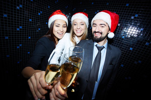 Three Business Partners In Santa Caps With Flutes Of Champagne Celebrating Xmas