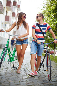 Portrait Of Girl And Guy With Bicycles Walking Down Park And Talking