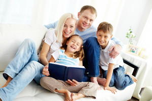 Portrait Of Happy Family With Two Children Looking At Camera And Laughing