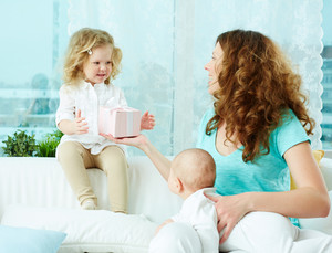 Happy Mother Giving A Present In Giftbox To Her Little Daughter