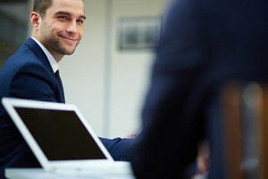 Young Businessman Looking At Colleague At Meeting