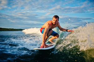 Sporty Man Surfboarding In The Sea