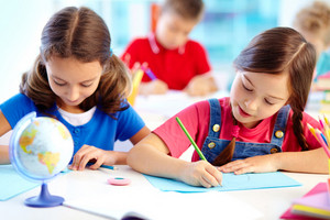 Portrait Of Lovely Girls Drawing At Workplace With Schoolboys On Background