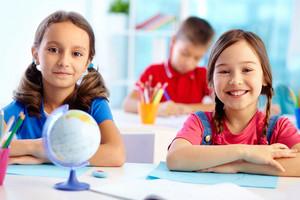 Portrait Of Cute School Girls Sitting At Their Desk